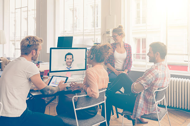 A team communicating with a remote colleague via video conferencing.