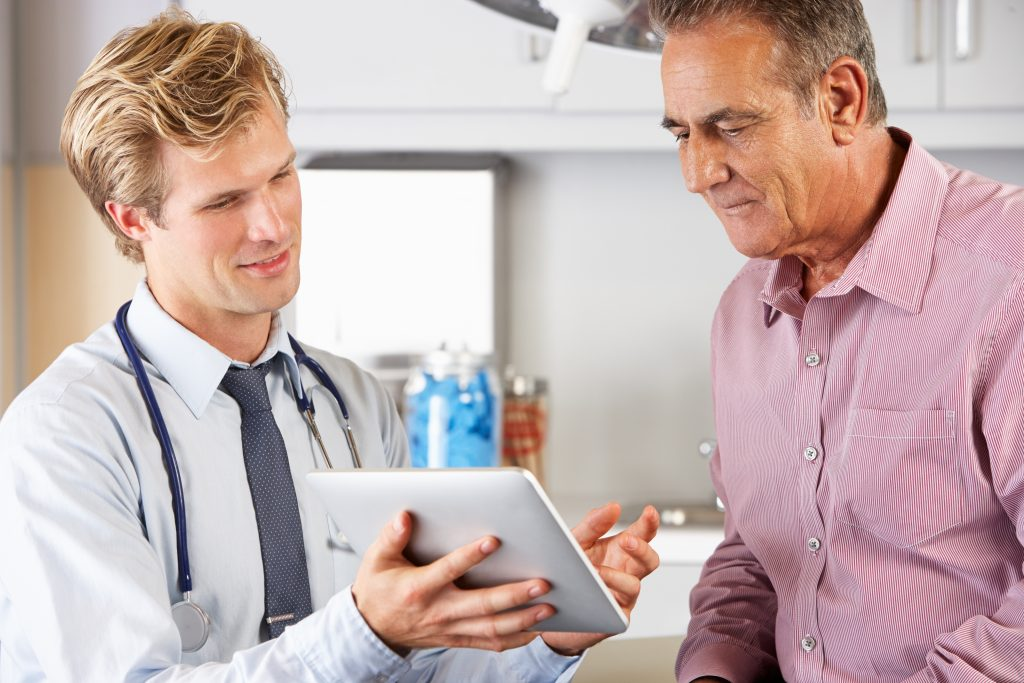 doctor showing treatment method on tablet to patient with HIPAA compliance