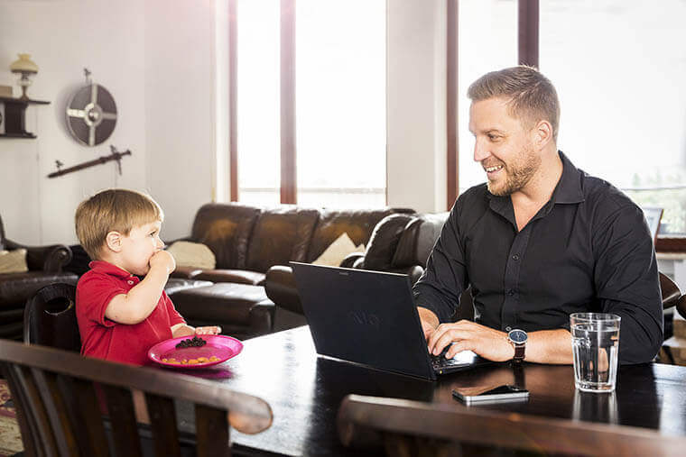 Father working from home while caring for his son.