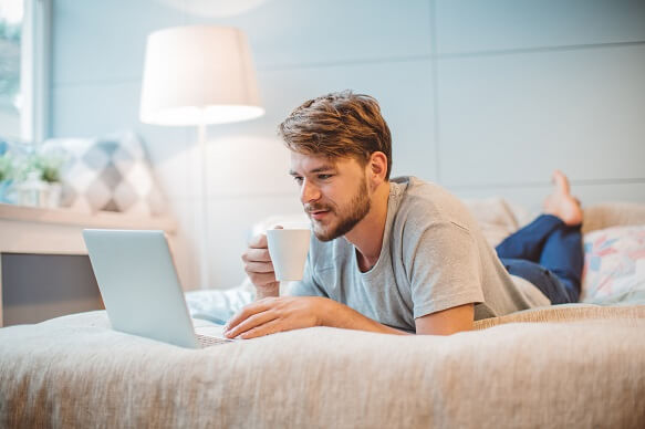 Man working on a laptop on a bed