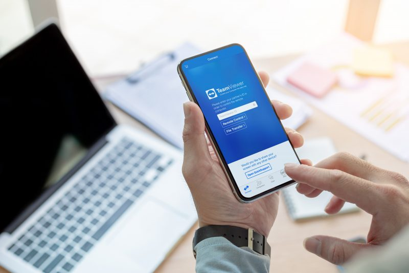 man using TeamViewer remote access from iphone