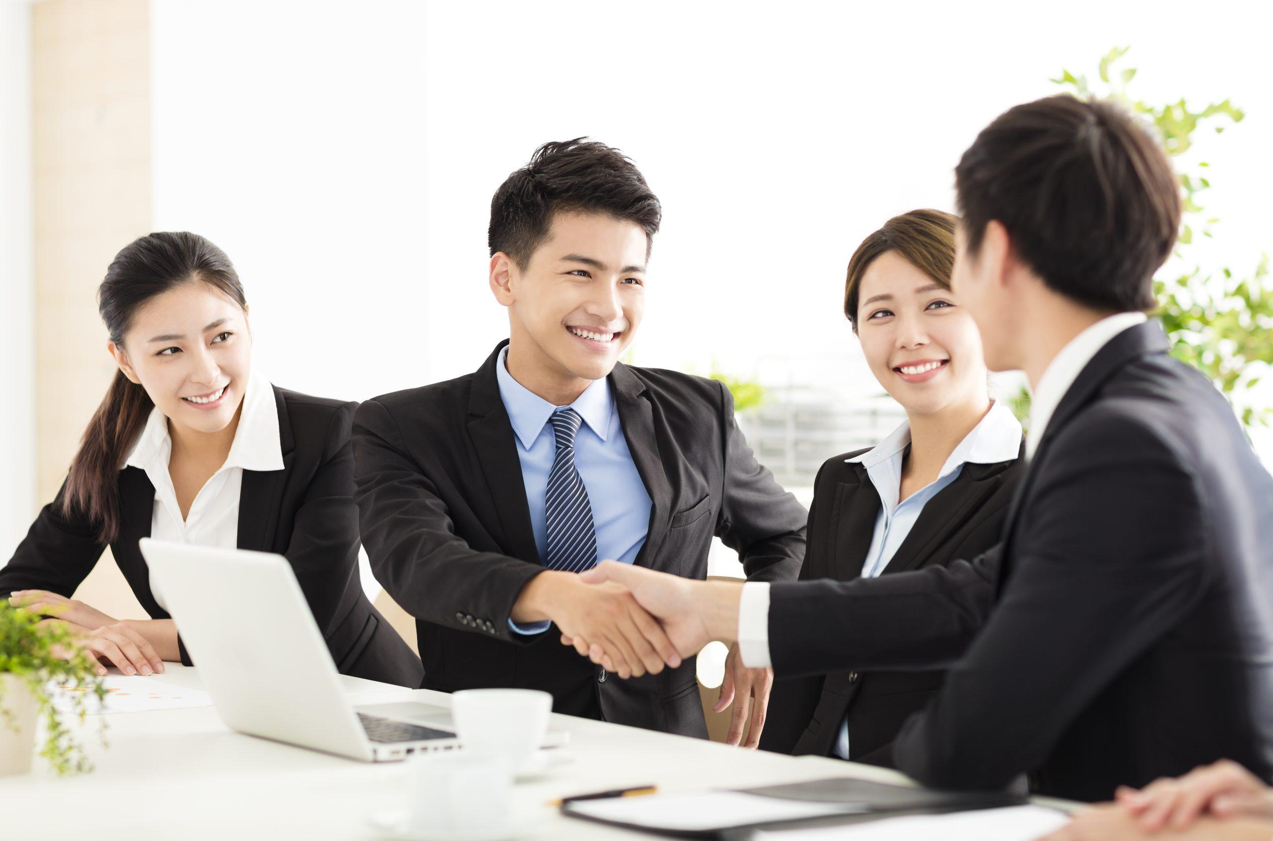 nhóm bốn nam nữ doanh nhân thành đạt mặc vest vui vẻ bắt tay tại cuộc họp trong phòng với laptop, ly cafe, cây cảnh trên bàn