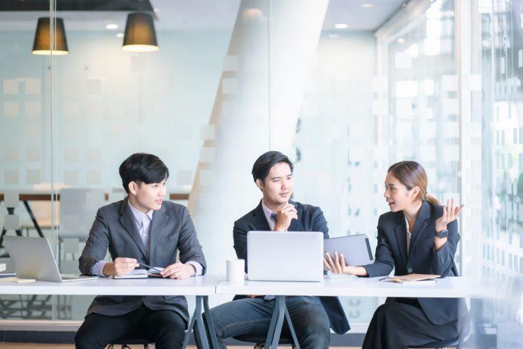 ba nam nữ đồng nghiệp châu Á vui vẻ trò chuyện tại văn phòng sử dụng phần mềm Quay màn hình nhẹ TeamViewer trên laptop và tablet màu bạc