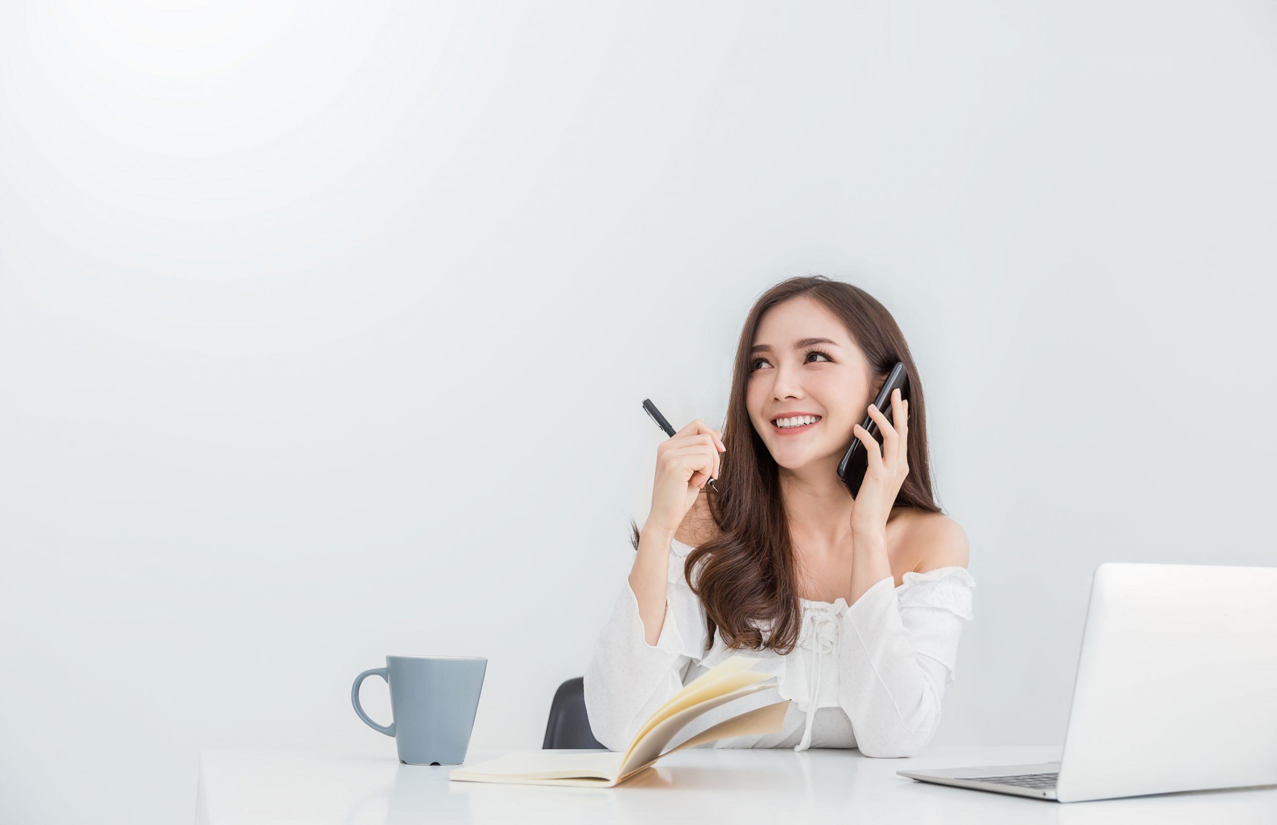 アジアの女の子の自宅のラップトップで仕事と電話で話しています。