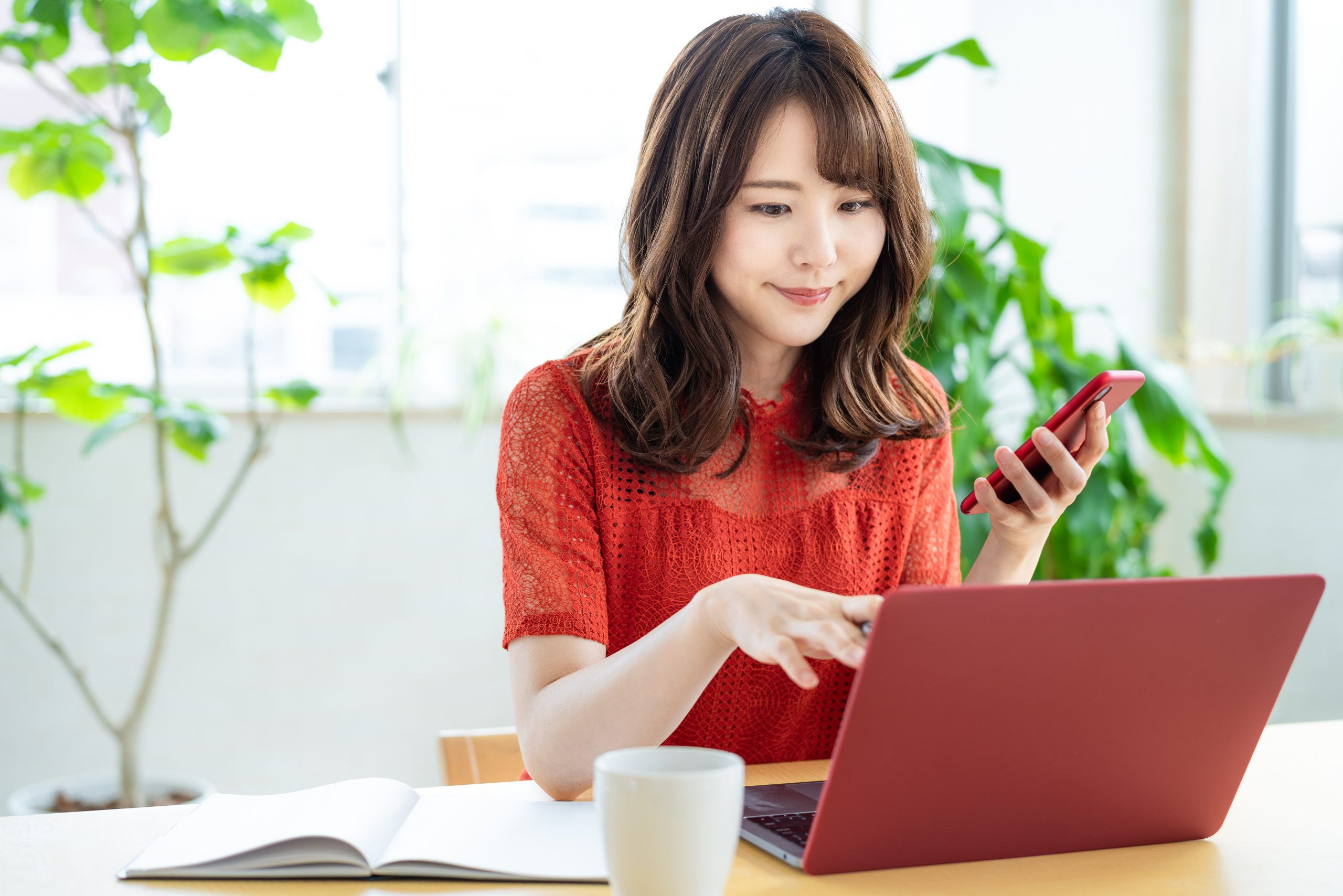 asian woman working remotely using TeamViewer Mac Remote Desktop while holding iphone