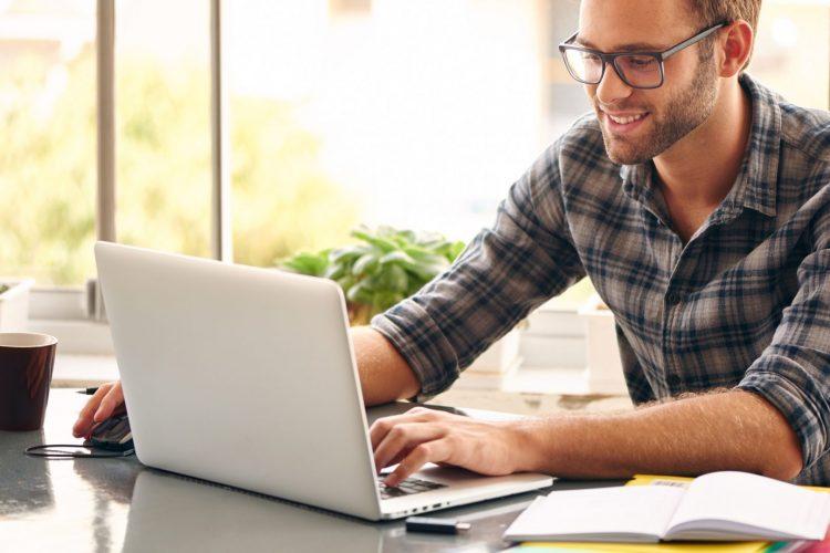 man wearing casual glasses using TeamViewer Remote Control on macbook