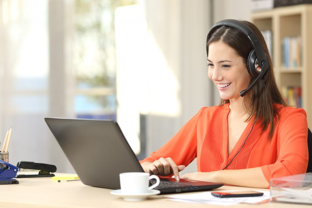 woman wearing headphone working from home using TeamViewer remote desktop for windows