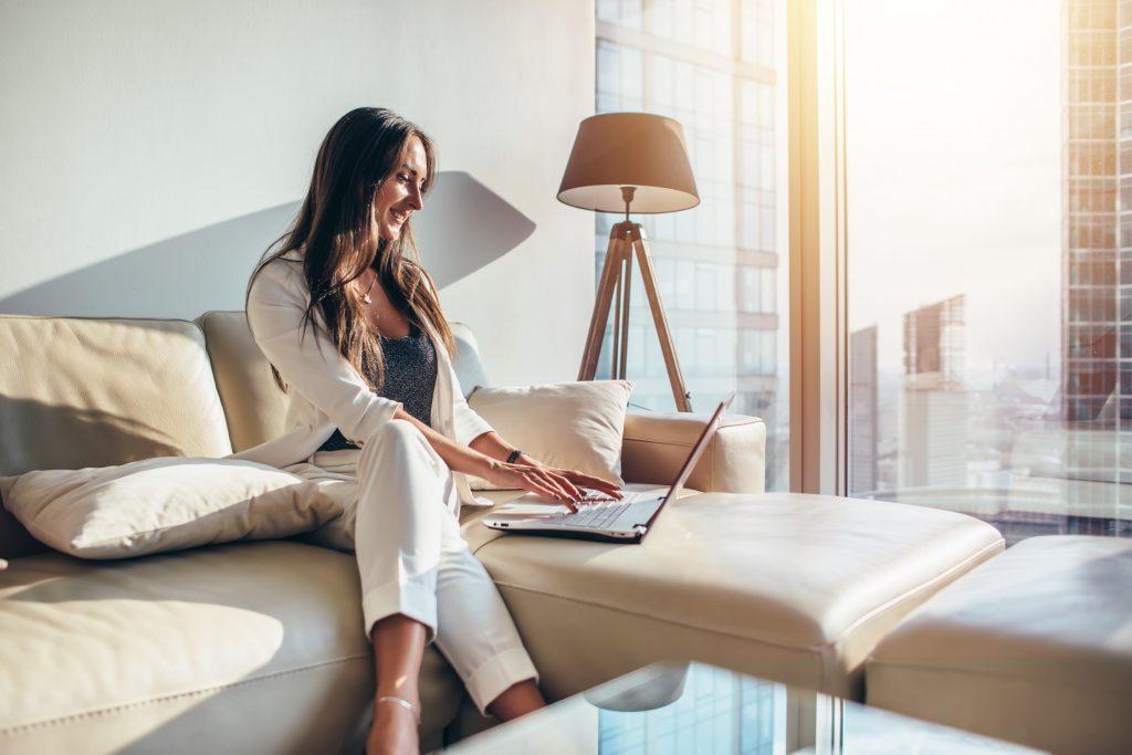 Elegant försäljartjej i vit dräkt ansluter till affärsmöte online på en bärbar dator med hjälp av TeamViewer i vardagsrummet i en lyxig lägenhet