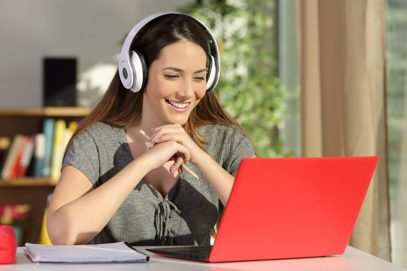 smiling girl remote learning wearing headphones at home